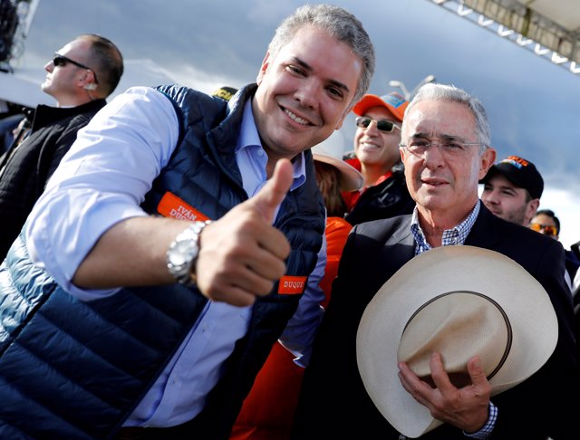 FILE PHOTO: Colombian former president Alvaro Uribe (R) and right-wing president