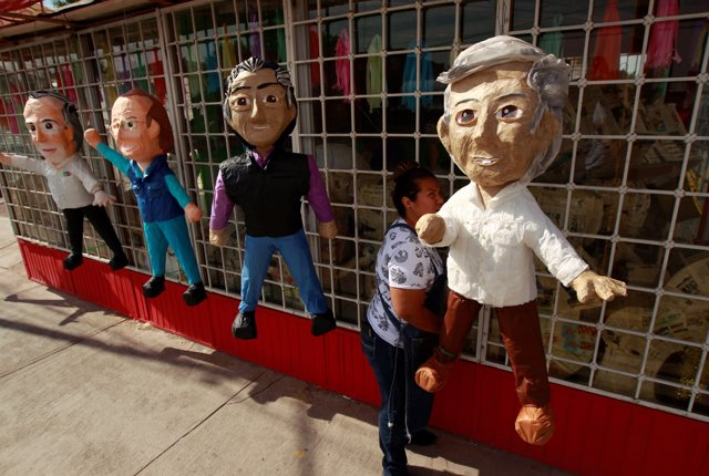 A woman hangs up pinatas for sale depicting Mexican presidential candidates Andr