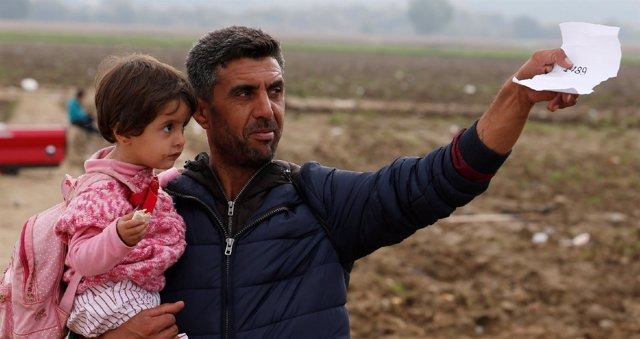 Un refugiado con su hija en brazos