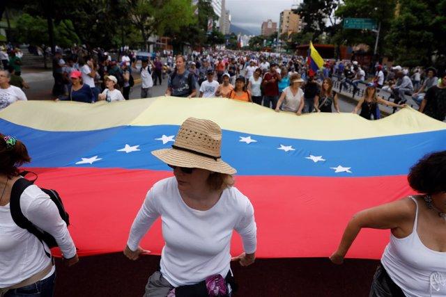 Manifestación de la oposición con una bandera de Venezuela en Caracas