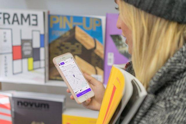 Chica viendo la aplicación de Cabify en el móvil