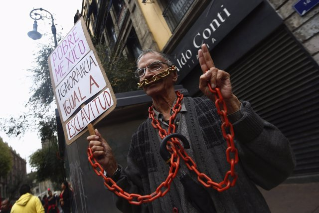 A man holds a poster while wearing chains, during a march marking the 46th anniv