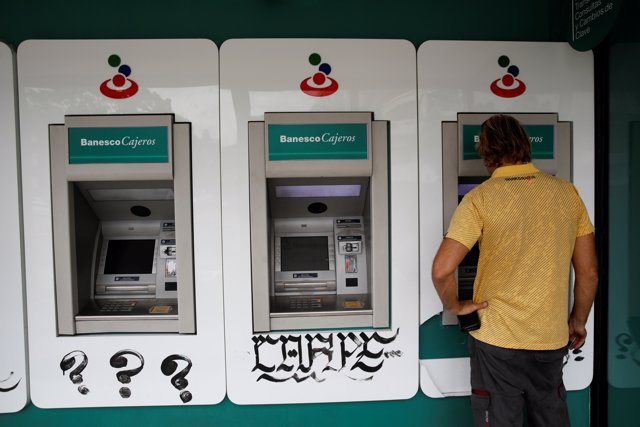A man uses an automated teller machine (ATM) at a Banesco bank branch in Caracas