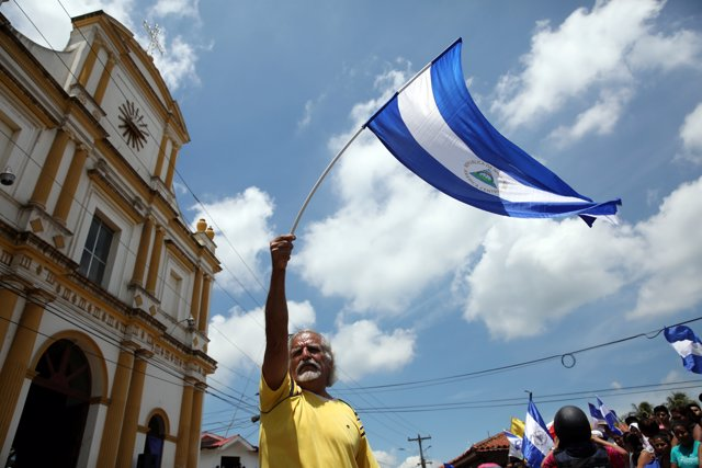 A man waves a national flag during a visit by Catholic leaders as anti-governmen