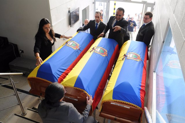 Funeral workers arrange Ecuadorean flags on top of coffins holding the dead bodi