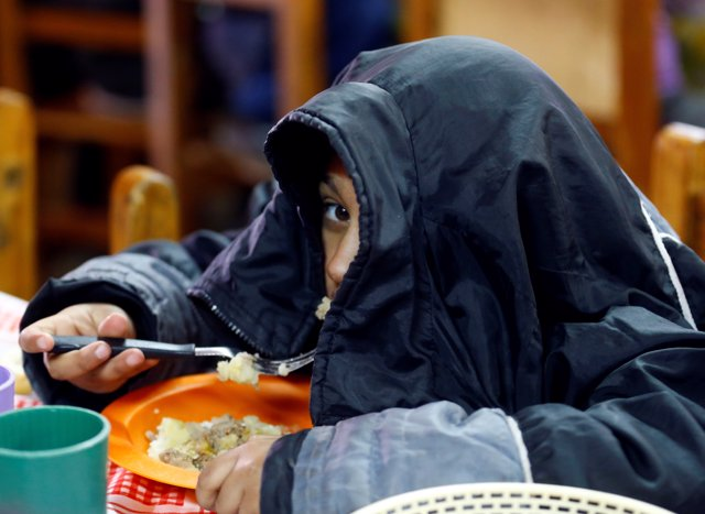 """A child eats at the community youth center """"Che Pibe"""" in Villa Fiorito, on the o"""