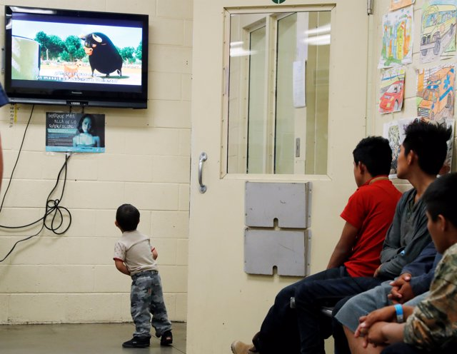 A detained immigrant child watches a cartoon while awaiting the arrival of U.S.
