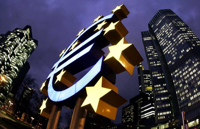 The illuminated euro sculpture is seen in front of the European Central Bank's (