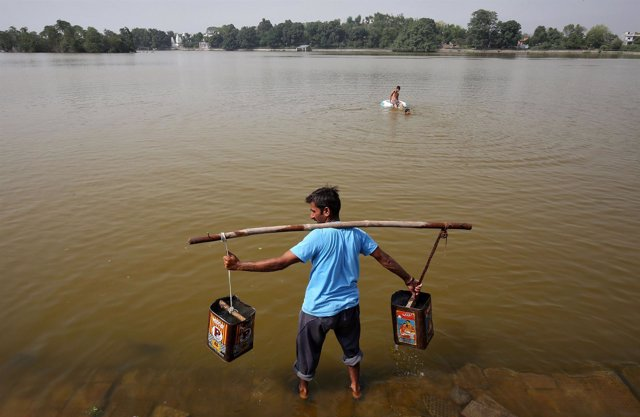 Un hombre recoge agua en Jammu, India