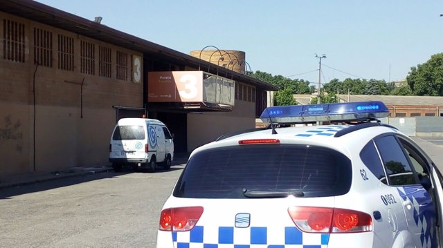 Un coche de la Guardia Urbana y una furgoneta de Ilnet en los Camps Elisis