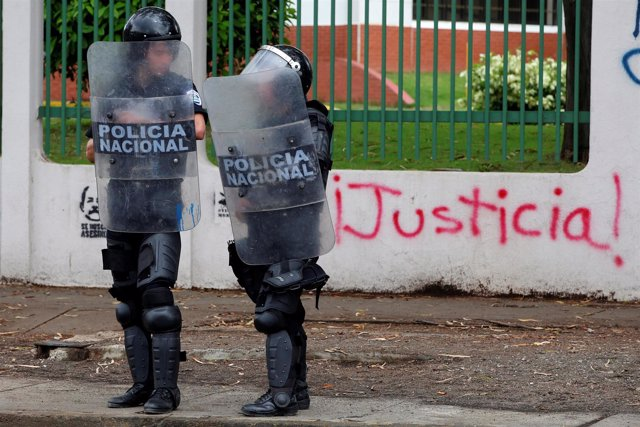 """Riot police officers stand in front of a graffiti that reads """"Justice"""" during a"""