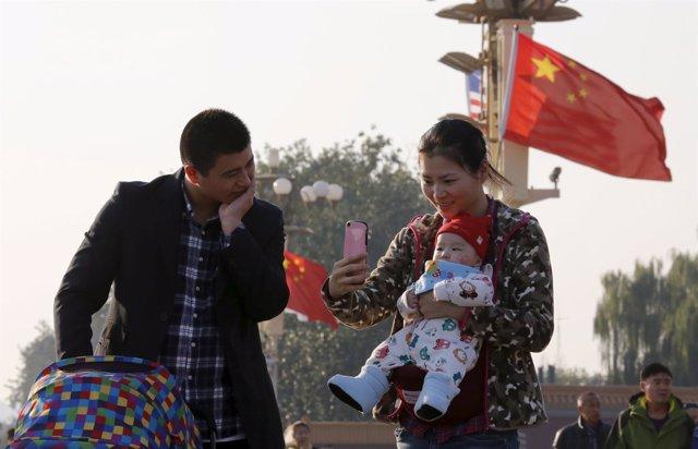 Una pareja china con su hijo en la plaza Tiananmen, en Pekín