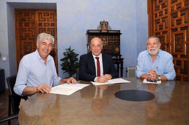 Antonio Ruiz (centro) firma el convenio