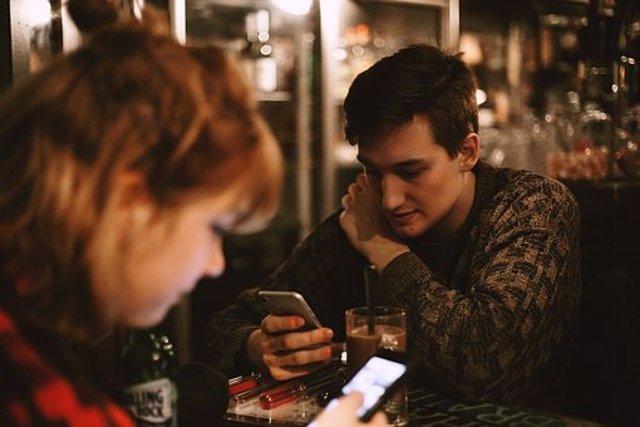Dos personas mirando el móvil