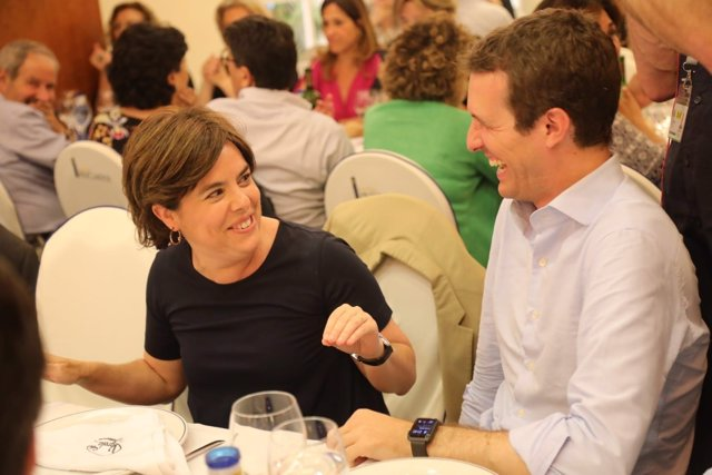 Soraya Sáenz de Santamaría y Pablo Casado rien en una cena del PP