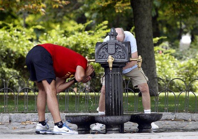 Dos personas se refrescan en una fuente por el calor
