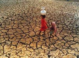 Dos niñas caminan por un terreno agrietado por la sequía