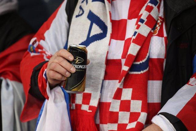 Un aficionado croata sostiene una cerveza