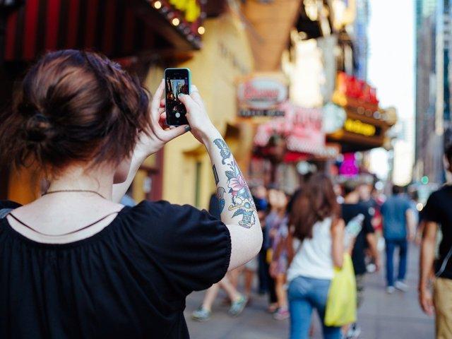 Chica fotografiando una calle