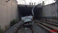 Un cotxe cau a les vies del tren a Vic (Barcelona) (BOMBERS DE LA GENERALITAT)