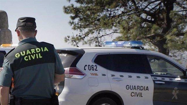 Agente de la Guardia Civil junto a un coche patrulla