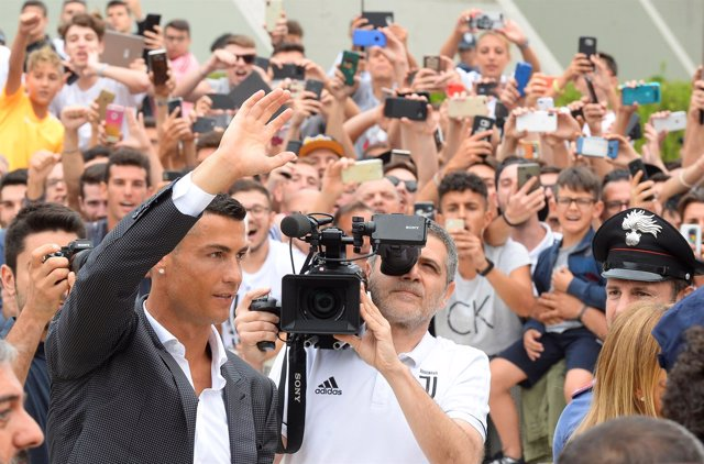 Cristiano Ronaldo waves as he arrives at the Juventus' medical center in Turin,