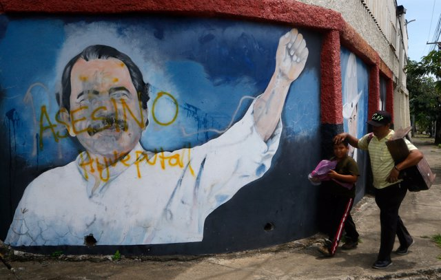 People walk in front of an image of Nicaragua's President Daniel Ortega in Manag