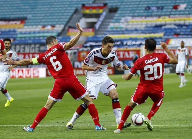 Ozil controla el balón ante la defensa de Gibraltar