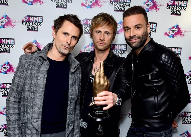 Matt Bellamy, Chris Wolstenholme and Dominic Howard of Muse holding the award fo
