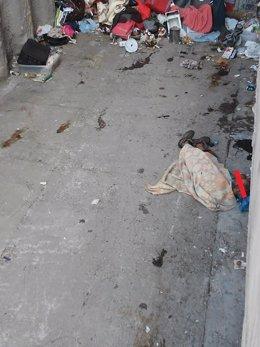 Una persona sin hogar duerme entre basuras