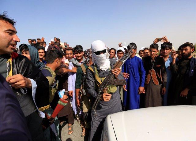 Un talibán posa armado con civiles en Nangarhar en la tregua