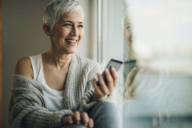 Mujer madura feliz, móvil, menopausia, canas, sonrisa