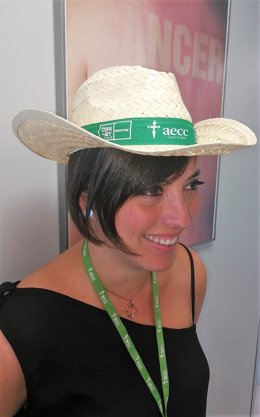 Mujer con sombrero de AECC contra el cáncer de piel