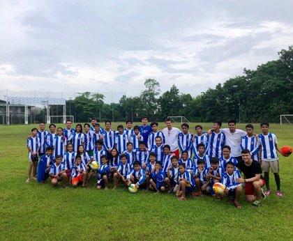 Siete voluntarios entregan material del RCD Espanyol a niños en Filipinas en un proyecto de deporte y salud