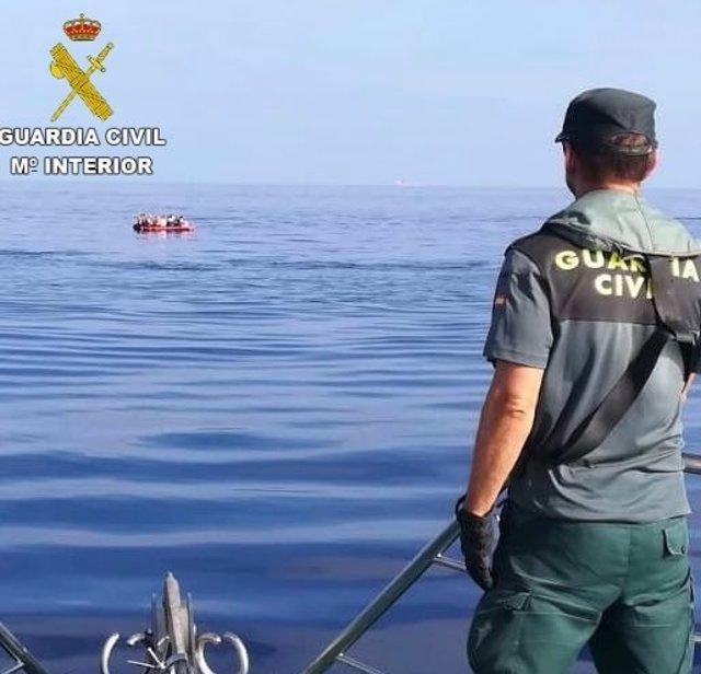 Un agente observa la patera con los inmigrantes a bordo