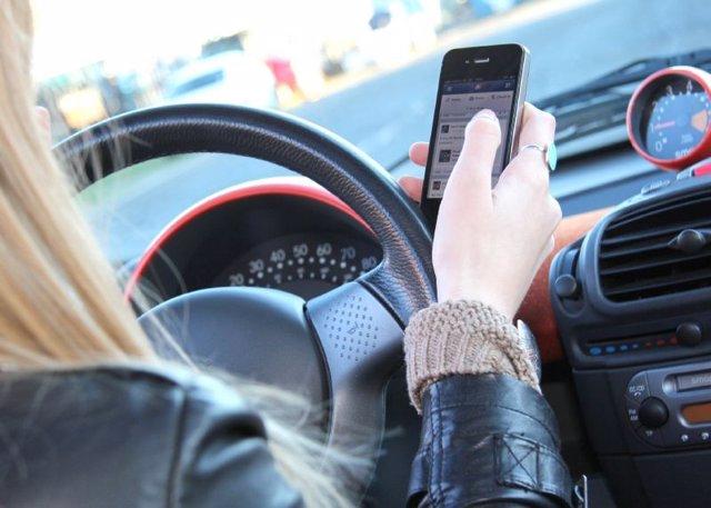 Una mujer usa su teléfono móvil mientras conduce
