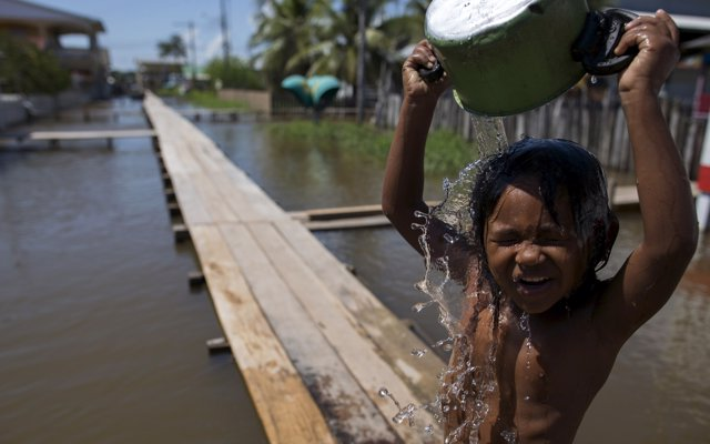 A boy pours water on himself as he stands on a makeshift walkway above a flooded