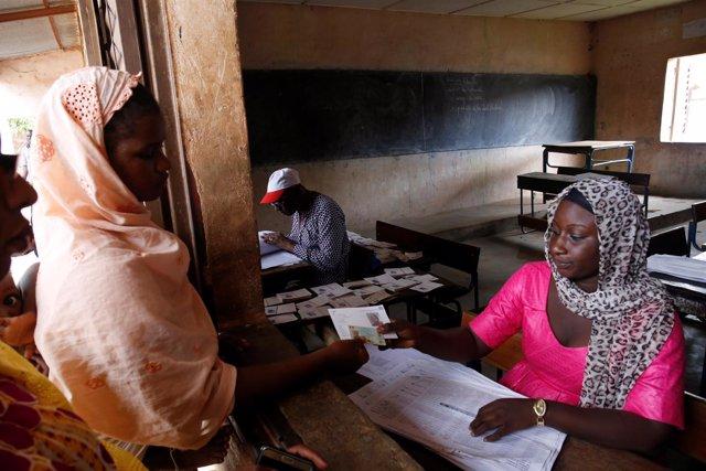 Una mujer recoge su tarjeta de votación en la capital de Malí, Bamako