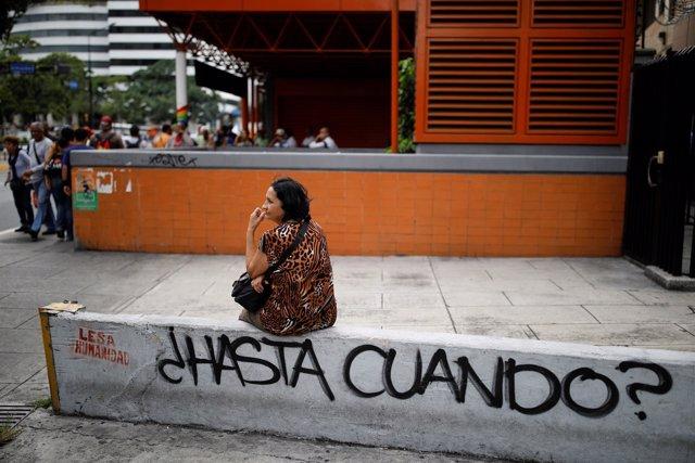 Una mujer espera el autobús tras salir del metro de Caracas por un apagón