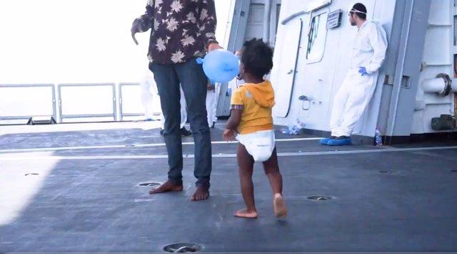 Una niña migrante camina por la cubierta de un barco tras ser rescatada del mar