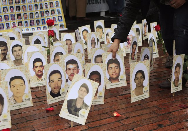 A woman locates a portrait among of a group of portraits of missing people durin