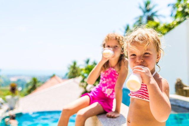 Hambre en la piscina, dos niñas bebiendo yogur, verano, vacaciones
