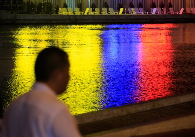 The colors of the Colombian flag are reflected in a canal next to the convention