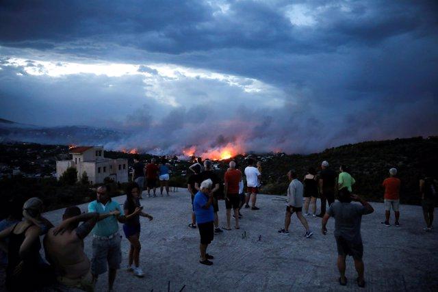 Un grupo de personas contempla las llamas del fuego en Rafina, cerca de Atenas