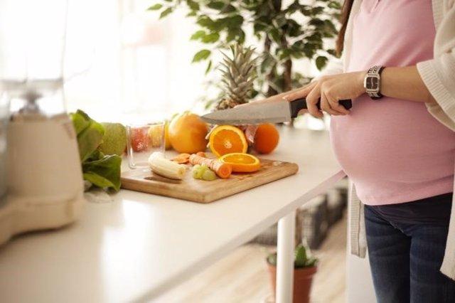 Embarazada, cocinar, naranjas
