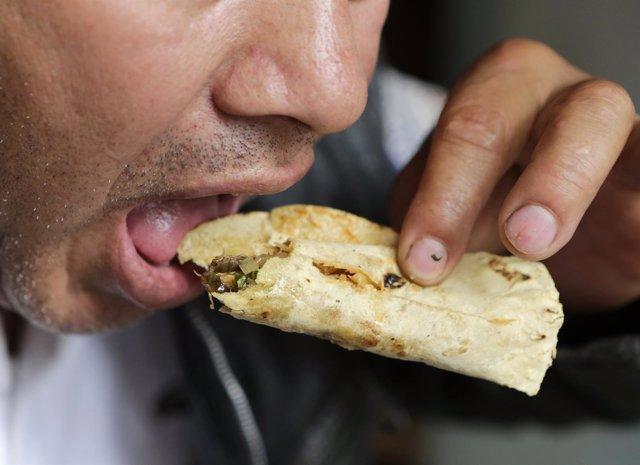Hombre comiendo un taco en México.