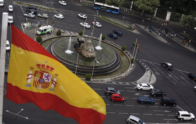 A Spanish flag flutters above the Cibeles fountain as they are seen from observa