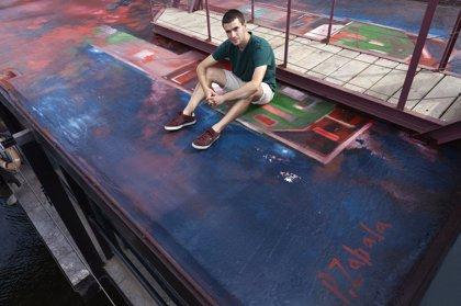 Un estudiante de Bellas Artes de la UPV/EHU pinta un mural en el Puente Colgante por su 125 aniversario