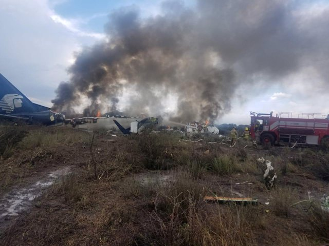 Firefighters douse a fire as smoke billows above the site where an Aeromexico-op