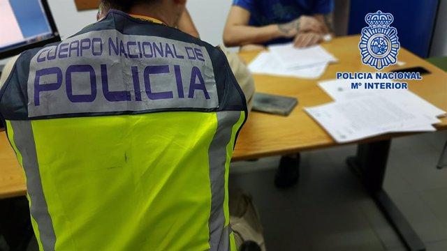 Agentes de la Policía Nacional, con uno de los detenidos